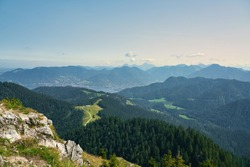 Panorama view of the mountains, a big forest and the lake Tegernsee in late summer (autumn). Alpine landscape with warm and soft colors. Vacation and hiking in the Bavarian Alps, Germany, Europe