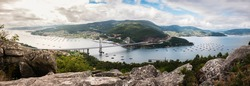 Panorama view of the Ria de Vigo estuary from Redondela on a cloudy Summer afternoon, with the recently extended Rande bridge on the center and the Atlantic Ocean on the left.