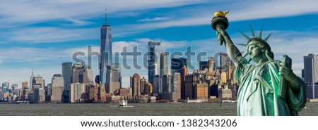 Panorama view of The Statue of Liberty in foreground and New York City skyscrapers in background, Landmarks of New York at Lower Manhattan, Financial district, New York City, USA.