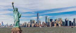 Panorama view of The Statue of Liberty with One World Trade Center and Manhattan downtown sky scraper with cloud blue sky background, Financial district lower Manhattan, New York City, USA.