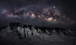 Panorama view of universe space shot of nebula and milky way. Milky way galaxy on hill under amazing starry blue night sky. Silhouette of Snow Mountain Grand Canyon of Chonburi, Stonehenge of Thailand
