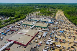 Panorama view on flea market roof top with miscellaneous items and crowds of buyers and sellers walking street in Englishtown NJ USA