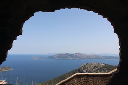 Panorama view over island in the mediterranean ocean, from a cliff with some building ruin who gives the picture a natural frame
