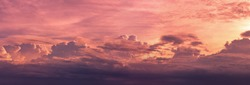 Panorama view red and purple sunset sky. Beautiful cloudscape in heaven sky. Nature background. Golden and dark fluffy clouds with sunlight. Beautiful clouds layer. Majestic sky for wallpaper.