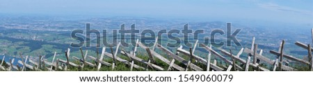 Panorama vista of Switzerland landscape Lake Lucerne, distant alps mountains.  Handcrafted rural wooden fence marks edge of cliff to plains below. #1549060079