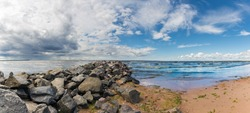 Panorama with a stone breakwater going into the sea. The contrast of a rainy sky on the left and a clear blue sky with white clouds on the right. Light waves  run to the sandy shore