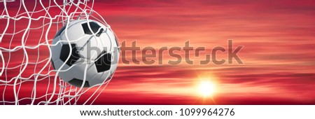 Panorama with classic football hitting the net of a goal in front of a sunset and evening sky (3D Rendering) #1099964276