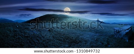 panorama with rock on the grassy hill in mountains. beautiful summer landscape in full moon light. amazing nature scenery. dramatic cloudy sky at night