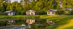 Panorama with row of colorful wooden vacation home reflected in a pond at recreation park in the middle of nature in the Netherlands