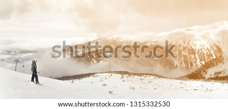 Panorama with snowboarder sit with snowboard in hands sits on big rock on mountains backdrop view. Bansko, Bulgaria #1315332530