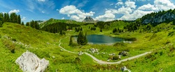 panorama with the Körber lake into the mountains from Bregenzerwald, surrounded from flowered meadows and high steep mountains, grass, flowers and forests, sunny summer day with clouds, Austrian alps