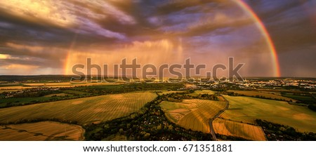 Panoramic, aerial photo of dramatic rainbow over european landscape. Large late evening rainbow over city and hills in agricultural landscape. Rainbow over Litovelske pomoravi national nature reserve.