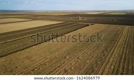 Panoramic aerial view of agricultural cultivated field with tractor performing fall tillage.
