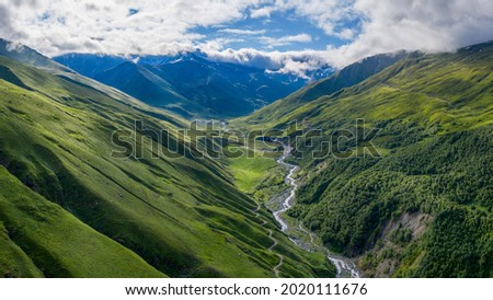 Panoramic aerial view of Balkarsky Cherek river gorge and Great Caucasus Range on sunny summer day. Kabardino-Balkaria, Caucasus, Russia.