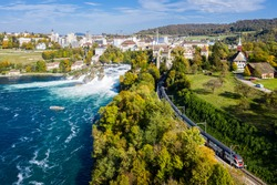 Panoramic aerial view of Rhine Falls and cityscape of Neuhausen am Rheinfall town, Switzerland. Red Swiss train, and tourist boats in waterfall. Cliff-top Schloss Laufen castle, Laufen-Uhwiese.