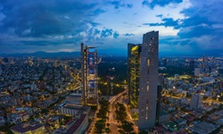 Panoramic aerial view of the famous Reforma avenue full of trees and huge office buildings illuminated by the night lights of the city