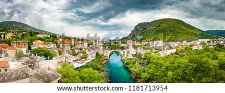 Panoramic aerial view of the historic town of Mostar with famous Old Bridge (Stari Most), a UNESCO World Heritage Site since 2005, on a rainy day with dark clouds in summer, Bosnia and Herzegovina
