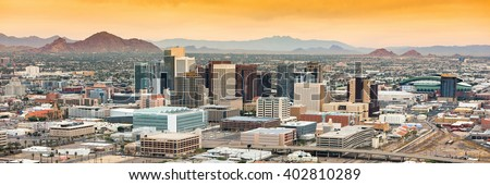 Panoramic aerial view of the Phoenix, Arizona skyline against the day\'s blue sky.