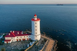 Panoramic aerial view of the Tolbukhin lighthouse. Artificial rocky island in the Gulf of Finland. The oldest Russian lighthouse. Baltic Sea. Stony coast. Summer day. Blue sky