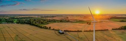 Panoramic aerial view of wind turbine in wheat fields in summer with biogas plant. Aerial view of Eolian generator in a beautiful wheat fields with agricultural factory in the countryside.