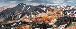 Panoramic amazing Icelandic landscape of colorful rainbow volcanic Landmannalaugar mountains, at famous Laugavegur hiking trail with dramatic snowy sky, and red volcano soil in Iceland.