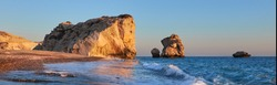 Panoramic Aphrodite rock Cyprus in soft evening light, curvy waves in the foreground touristic attraction of so called love rock