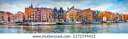 Panoramic autumn view of Amsterdam city. Famous Dutch channels and great cityscape. Colorful morning scene of Netherlands, Europe. Traveling concept background.