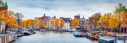 Panoramic autumn view of Amsterdam city. Famous Dutch channels and great cityscape. Gloomy morning scene of Netherlands, Europe. Traveling concept background.
