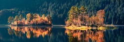 Panoramic autumn view of Eibsee lake. Unbelievable morning scene with first sunlight glowing small islands on bottom of the Zugspitze peak, Bavaria, Germany, Europe. Beauty of nature concept backgroun