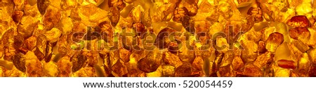 panoramic background  closeup luminous  baltic amber stones rectangular lie on a flat surface #520054459