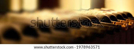 Panoramic background of bottles of red wine on a wooden shelf. Wine concept web banner. Сток-фото ©