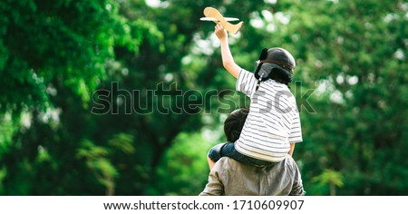 Panoramic background of father and son on his shoulder playing paper plane, spending time together at fresh green park in afternoon sunlight, the concept of family outdoor, daddy hero. Single Daddy.