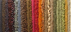 Panoramic background, spices and herbs for design packaging with food or websites headers.  Bright seasonings scattered on table in form rainbow.