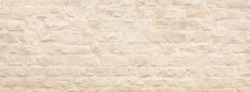 Panoramic background - structure of an old natural stone wall with beige plaster