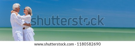 Panoramic banner image of a happy senior man and woman couple together embracing by sea on a deserted tropical beach with bright clear blue sky