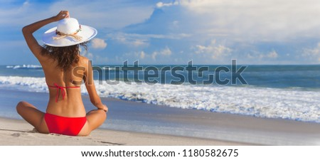 Panoramic banner image of sexy young brunette woman or girl wearing a red bikini and sun hat sitting on a deserted tropical beach with a blue sky