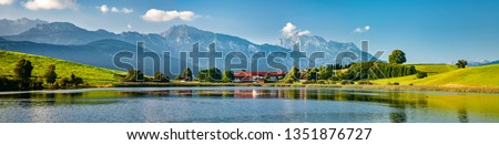Panoramic bavarian landscape with small village by a lake, the alps behind, Allgau, Bavaria, Germany #1351876727