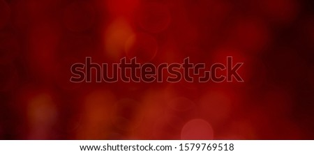 Panoramic Beautiful blurred dark Red and Orange Background with bokeh lights. Wide screen holiday Texture, defocused. Can be used for design greetings cards, invitations or promotional flyers. #1579769518