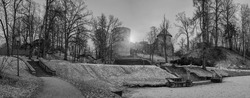 Panoramic black and white image of Cesis medieval castle ruins in a beautiful park with frozen lake and stone stairs in Cesis, Latvia