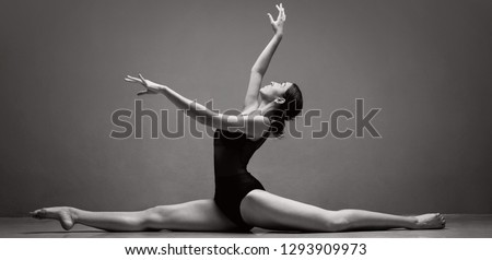 Panoramic black and white view of beautiful ballet dancer doing splits stretching legs with pose on stage, indoors studio. Elegant performer, concept flexibility, power discipline, physical work.