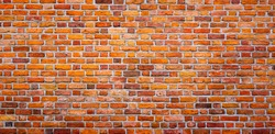 Panoramic Bright Orange Red Brick Wall Background. Vintage Brickwall Texture. Wide Angle Grunge Web banner or Wallpaper With Copy Space.