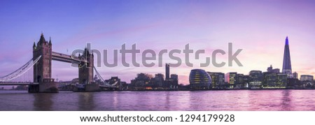 Panoramic city skyline of London across River Thames with view of Tower Bridge, at twilight