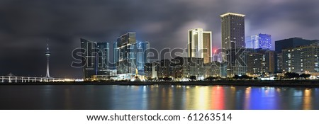 Panoramic cityscape in night with skyscraper and buildings and river in Macao, China.