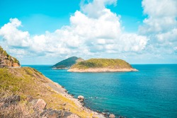 Panoramic coastal Con Dao view from above, with waves, coastline ,clear sky and road, blue sea and mountain.