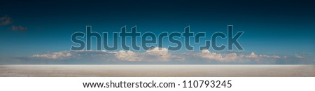 panoramic desert landscape with deep blue sky and clouds