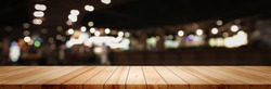 Panoramic empty clean wood counter table top on blur street night cafe background use for pub coffee shop montage dark scene, Blurry wide wooden texture shelf bar in luxury restaurant kitchen backdrop