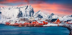 Panoramic evening view of popular tourist destination - Lofoten Islands archipelago. Colorful houses on the shore of Norwegian sea. Wonderful winter scene of Sakrisoy fishing village.