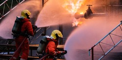 Panoramic Firefighter team use water fog type fire extinguisher to fight with flame from oil pipeline leak and explosion on oil rig and natural gas station. Firefighter and industrial safety concept.