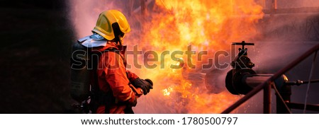 Panoramic Firefighter use water fog type fire extinguisher to fight with fire flame from oil pipeline leak and explosion on oil rig and natural gas station. Firefighter and industrial safety concept.