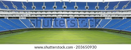 Panoramic football stadium with green grass and blue seats
